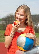 Austria, Teenage girl with apple and soccer ball, smiling, portrait