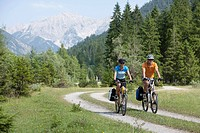 Austria, Tyrol, Man and woman cycling through dirt track