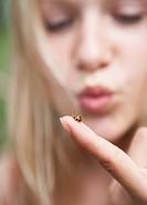 Austria, Teenage girl looking at ladybird on her finger