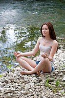 Austria, Young woman doing meditation