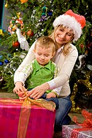 Woman opening Christmas presents with her son.
