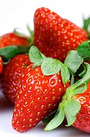 forefront of a group of fresh strawberries on a white background