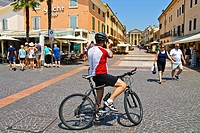 Cyclist stopped in street to take photo, Bardolino, Lake Garda, Italy