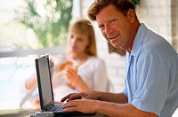 Man Using Laptop with Woman Reading