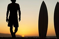 man with surfboard watching sunset at the beach