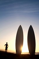 man watching sunset at the beach with surfboards