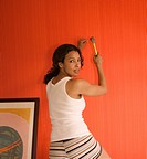 Young Woman Hammering a Nail into Red Wall