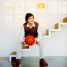 Young Man Sitting on Stairs and Holding Basketball