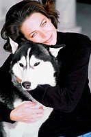 Young woman holding pet husky dog