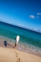woman carrying paddle board down the beach to the ocean