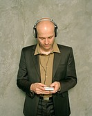 Businessman with bald head listening to personal CD player