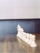Chess pieces in row on wooden table