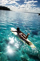 young woman paddling on long board in turquoise lagoon