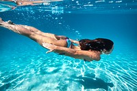 woman free diving in crystal clear turquoise lagoon