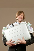 Businessman holding suitcase full of Euro notes