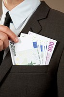 Businessman grasping in jacket pocket with Euro notes