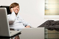 Happy businessman at desk on the phone