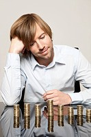 Smiling man at desk looking at stacks of coins