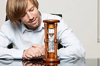 Man at desk looking at hourglass