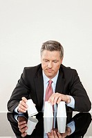 Businessman playing shell game with plastic cups at desk