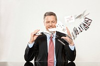 Smiling businessman playing with cards at desk