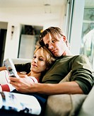 Couple Relaxing on Couch and Looking at Cell Phone