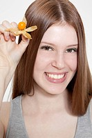 Brunette young woman holding cape gooseberry