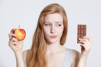 Redheaded young woman holding apple and chocolate