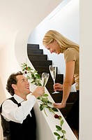 Couple holding champagne glasses on staircase decorated with red roses