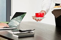 Coffee and pastry is being served for woman at desk (thumbnail)