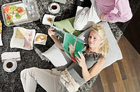 Couple on rug with food and magazine