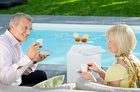 Senior couple drinking espresso by the poolside