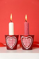 Two burning candles with heart_shaped candle holders