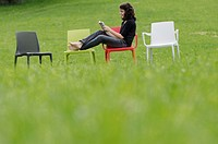 Girl sitting on plastic chair in meadow reading book