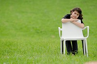 Girl with plastic chair in meadow sleeping