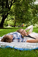 Young couple relaxing on blanket in meadow