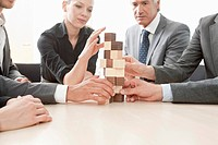 Five businesspeople stacking building blocks