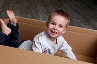 Enthusiastic boy inside cardboard box