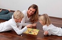 Mother and two children playing ludo on the floor