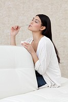 Dark_haired young woman eating yogurt