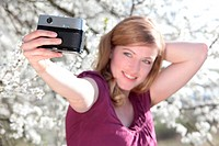 Woman taking picture of herself in front of blooming tree
