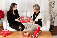 Mother and adult daughter handing over Christmas presents