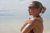 Woman on beach applying suntan lotion, Thailand