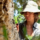 Woman Looking Through Magnifying Glass on Tree_Trunk