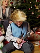 Boy Playing Toy Guitar in Front of Family