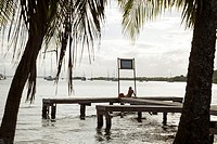 Man sitting on a dock looks towards the sea from Isla Colon, Bocas del Toro, Panama