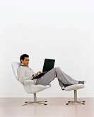 Man Reclining in Chair Using Laptop