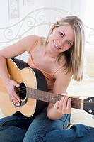 Young Woman Sitting on Her Bed with Guitar