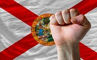 us state flag of florida with hard fist in front of it symbolizi