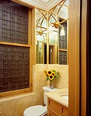 Ornate,patterned glass window in marble bathroom